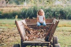 Fille s'asseyant sur un vieux chariot en bois Photos stock