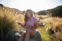 Fille s'asseyant sur une grande roche Photo stock