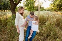 Fille s'asseyant sur une oscillation, un père et une mère enceinte poussant sur la nature, famille heureuse, parents, sourire, jo Photographie stock libre de droits