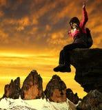 Fille s'asseyant sur une roche Image stock