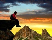 Fille s'asseyant sur une roche Images stock