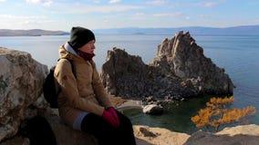 Fille s'asseyant sur une roche par la mer sur un fond de paysage étonnant banque de vidéos