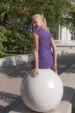 Fille s'asseyant sur une sphère en pierre Photo stock