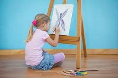 Fille s'asseyant vers le bas peignant un tableau Photographie stock