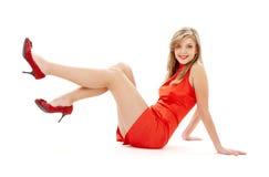 Fille s'asseyante dans la robe rouge avec des pattes vers le haut Images stock