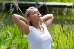 fille 20s blonde appréciant la chaleur du soleil en parc vert Photographie stock libre de droits
