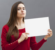 Fille 20s grave avec de longs cheveux bruns tenant un message sur le fond blanc Photo stock