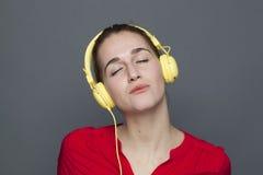 Fille 20s paisible pour le concept à la mode d'écouteurs Photo libre de droits