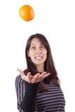 Fille \ 's projetant une orange Photographie stock libre de droits