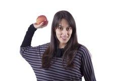 Fille \ 's projetant une pomme Photographie stock
