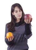 Fille \ 's retenant une pomme et une orange Photo libre de droits