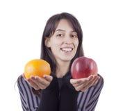 Fille \ 's retenant une pomme et une orange Photos libres de droits