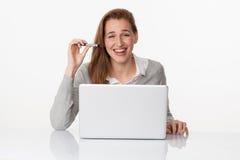 Fille 20s riante travaillant à son bureau avec satisfaction Image stock