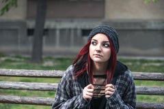 Fille sans abri, jeune belle fille rouge de cheveux seul s'asseyant dehors sur le banc en bois avec sentiment de chapeau et de ch photos stock