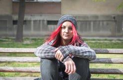 Fille sans abri, jeune fille rouge de cheveux seul s'asseyant dehors avec le chapeau et chemise soucieuse et déprimée après qu'el photographie stock libre de droits