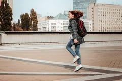 Fille sautant heureusement par le centre de la ville photos stock