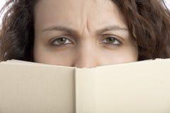 Fille sceptique avec le livre Photo stock