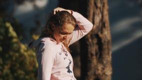 Fille se brossant les cheveux utilisant la paume de sa main Extérieur le jour d'été banque de vidéos
