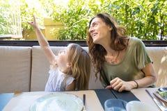 Fille se dirigeant avec le doigt à côté de la femme de sourire dans le restaurant photographie stock libre de droits