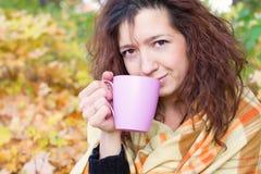 Fille se dorant avec une tasse disponible Image libre de droits