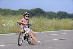 Fille se penchant contre la bicyclette Photo stock