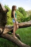 Fille se penchant contre un arbre Image stock