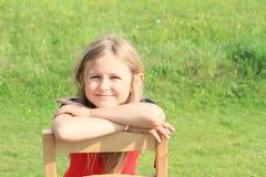 Fille se penchant sur la chaise Images libres de droits