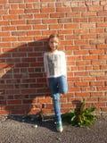 Fille se penchant sur le mur de briques Photographie stock libre de droits