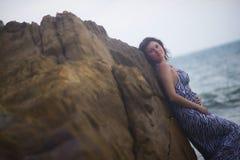 Fille se penchant sur une roche contre l'océan pendant l'été photographie stock libre de droits