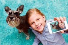 Fille se photographiant et son chien Photographie stock