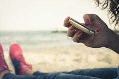 Fille se reposant sur la plage et à l'aide d'un téléphone portable Images libres de droits
