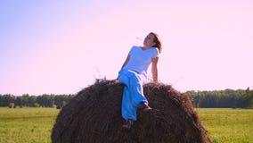 Fille se reposant sur une meule de foin au coucher du soleil Photo stock