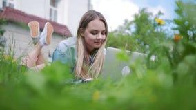 Fille se situant dans l'herbe, travaillant avec un ordinateur portable banque de vidéos