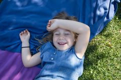 Fille se situant en parc riant avec les yeux fermés Photos stock