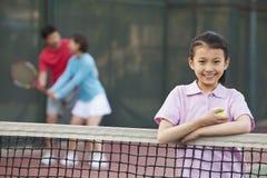 fille se tenant à côté du filet de tennis, parents jouant à l'arrière-plan photographie stock