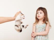 Fille se tenant avec elle de retour et tenant un chaton Photographie stock libre de droits