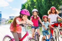 Fille se tenant avec la bicyclette et les amis de attente Images stock