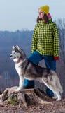 Fille se tenant avec un chien de traîneau de chien dans les montagnes Photos stock