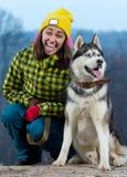 Fille se tenant avec un chien de traîneau de chien dans les montagnes Photo stock