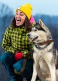 Fille se tenant avec un chien de traîneau de chien dans les montagnes Photos libres de droits
