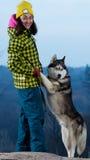 Fille se tenant avec un chien de traîneau de chien dans les montagnes Photo libre de droits