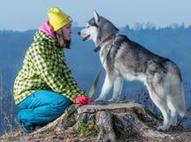 Fille se tenant avec un chien de traîneau de chien dans les montagnes photographie stock