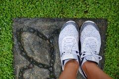 Fille se tenant dans des chaussures blanches sur l'herbe verte Images stock
