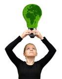 Fille se tenant dans l'ampoule d'énergie d'eco de mains Photographie stock