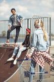 Fille se tenant dans le caddie tandis qu'amis se reposant sur la rampe au parc de planche à roulettes Photo libre de droits