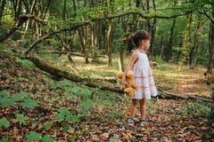 Fille se tenant dans le portrait en bois d'une fille dans les bois Ours Photos libres de droits