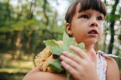 Fille se tenant dans le portrait en bois d'une fille dans les bois Ours Images stock