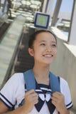 Fille se tenant et souriant à côté de l'escalator près de la station de métro Photographie stock libre de droits