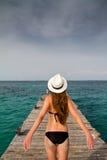 Fille se tenant à la jetée appréciant la brise de la mer Image stock