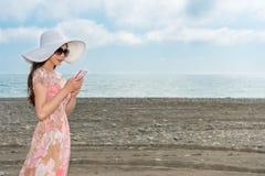 Fille se tenant sur la plage utilisant le mobile Image stock